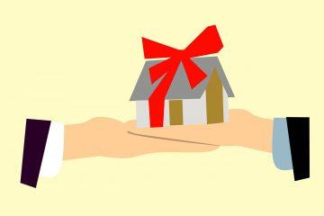 dos personas entregando una casa en venta con un lazo rojo