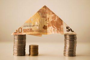 monedas sujetando un tejado de vivienda hecho con un billete