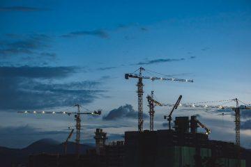 Grúas para construcción de viviendas de obra nueva en Valencia al atardecer